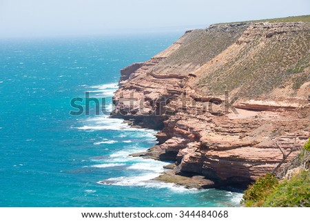 Scenic Aerial panoramic view of rough rock formation along coast of Kalbarri National Park in Western Australia, with wild waves of Indian Ocean crashing cliff, blue sky, horizon, copy space. - stock photo