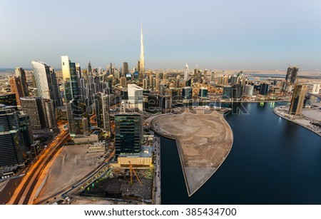Scenic aerial skyline of Dubai business bay with many modern skyscrapers at sunset. - stock photo