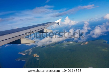 Scenic aerial view of Cocos Keeling Islands  territory of western Australia  through the tropical monsoonal clouds on a hot afternoon in summer from the aircraft as it descends into landing.