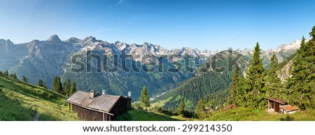 Scenic alpine panorama near Hochvogel, Germany with timber huts on a wooded plateau overlooking a spectacular view of rugged mountain ranges and peaks - stock photo