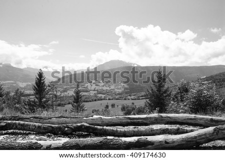 Scenic alpine view with cut logs at foreground. Annecy lake area (Haute-Savoie, France). Black and white photo. - stock photo