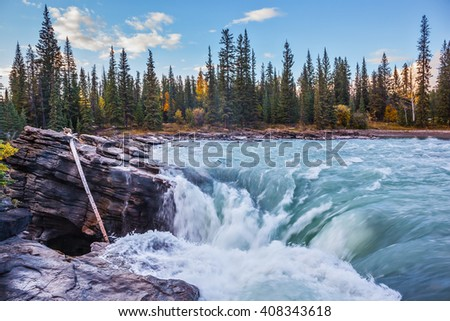 Scenic and powerful Athabasca Falls. Sunset  illuminates the surrounding mountains. Canada, Jasper National Park - stock photo