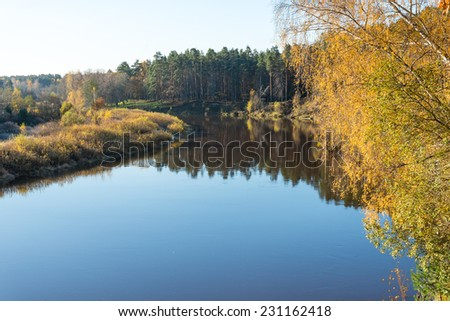 scenic autumn colored river in country with trees and reflections