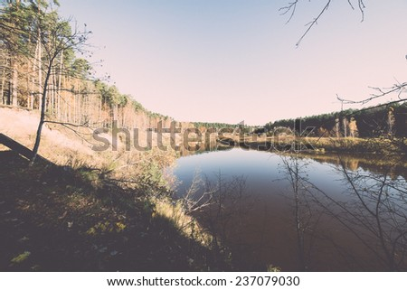 scenic autumn colored river in country with trees and reflections - retro, vintage style look