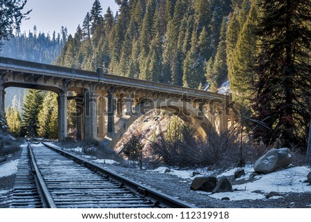 Scenic bridge cross a river with train tracks - stock photo