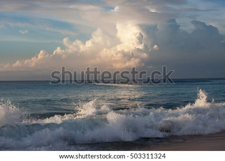 scenic colorful sunset on ocean with waves crushing at shore