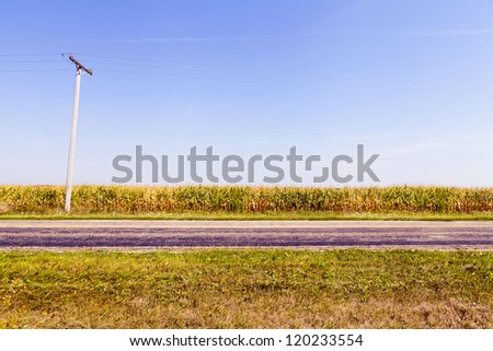 Scenic countryside empty road with blue sky - stock photo