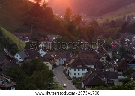 Scenic countryside landscape with beautiful mountain village at sunset. Germany, Black forest, Muenstertal. Aerial panorama.  - stock photo