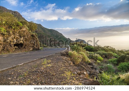 Scenic curvy road with fence on sunset, Tenerife, Canary islands - stock photo