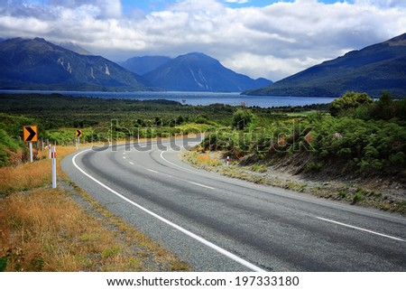 Scenic empty road in New Zealand. Mountains and a lake in the background. - stock photo
