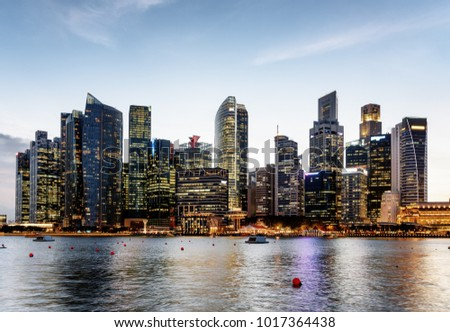 Scenic evening view of Marina Bay and downtown of Singapore. Skyscrapers and other modern buildings are visible on blue sky background. Singapore is a popular tourist destination of Asia.