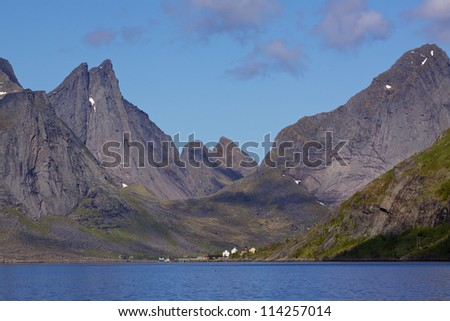 Scenic fjord Reinefjorden on Lofoten islands in Norway, with high rocky mountain peaks towering above the sea - stock photo