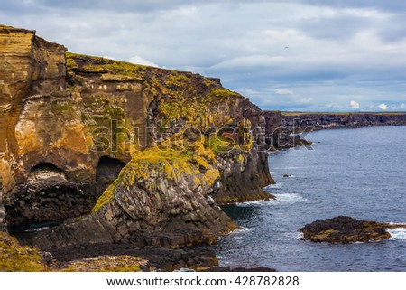 Scenic fjords on a cloudy summer day. Rocks covered with moss. Gorgeous Iceland. North sea coast - stock photo