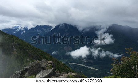 Scenic foggy mountain landscape with highway in the background - stock photo