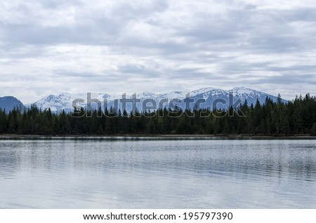 Scenic Glacial Lake With View of Evergreen Trees and Snow Capped Mountains - stock photo