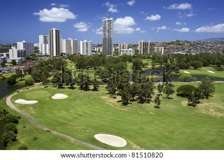 Scenic golf course with condominium buildings over looking in Hawaii - stock photo