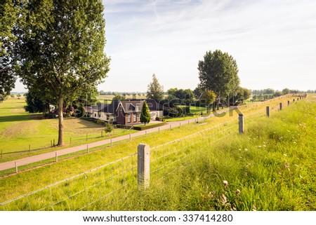 Scenic image of an old Dutch farmhouse situated underneath the river dike. The farmhouse was built in 1920. It is a sunny summer day with some cloudiness. - stock photo