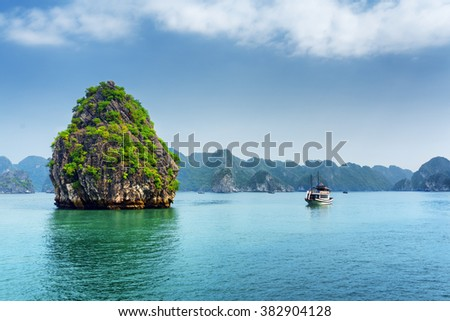 Scenic karst isle and tourist boat in the Ha Long Bay (Descending Dragon Bay) at the Gulf of Tonkin of the South China Sea, Vietnam. The Halong Bay is a popular tourist destination of Asia. - stock photo