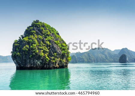 Scenic karst isle on blue sky background in the Ha Long Bay (Descending Dragon Bay) at the Gulf of Tonkin of the South China Sea, Vietnam. The Halong Bay is a popular tourist destination of Asia.