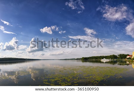 scenic lake in the summer park. Dramatic blue sky - stock photo