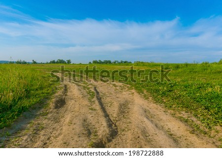 scenic landscape background green meadow blue sky with clouds and a wide rural road - stock photo