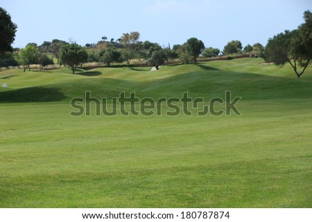 Scenic landscape of gently rolling greens on a golf course with carefully manicured grass for a healthy lifestyle enjoying exercise and sport - stock photo