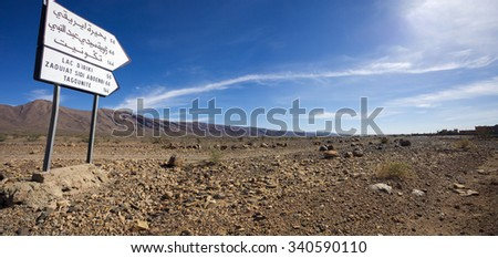 Scenic landscape of mountains and desert of stones with directional road sign with direction to Tagounite written in Arabic and French languages. Morocco 2010 - stock photo