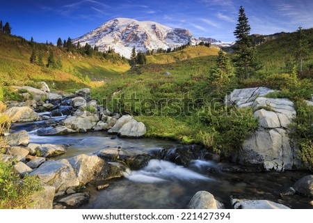 Scenic landscape of snowy mountain in the background and a small stream in the foreground - stock photo
