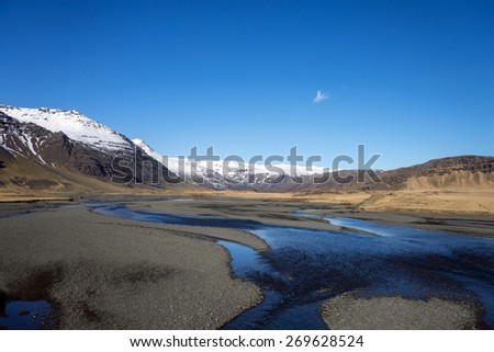 scenic landscape of southern Iceland; of snow-capped mountains, glaciers, grass fields, rivers and lakes formed by the melting ice from the mountains. - stock photo
