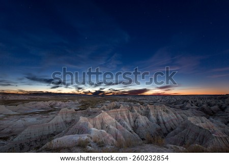 Scenic landscape of the constellation of Ursa Major, or Big Bear, over eroded mountains in the badlands of South Dakota in a starry evening sky - stock photo