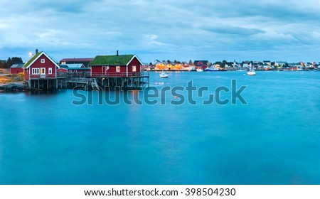 Scenic landscape on Lofoten islands, Reine with typical red fishing hut with grass on the roof near water in the evening  - stock photo
