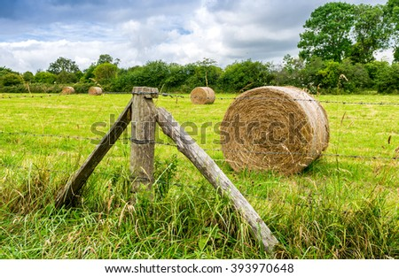 Scenic landscape with hay bales on Summer day, Normandy - France.