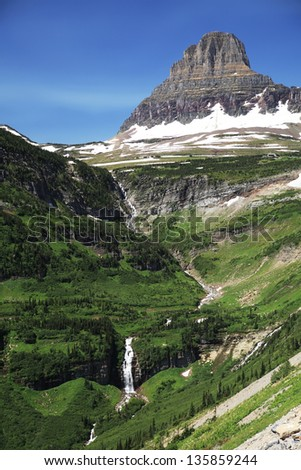 Scenic landscape with waterfall and glacial rock formation in background, Montana, U.S.A. - stock photo