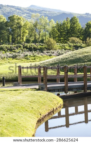Scenic landscape with wooden bridge alongside a pathway and mountainous background - stock photo