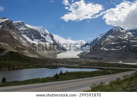 Scenic mountain road on lakeside with blue sky - stock photo