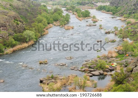 Scenic mountain valley with a wide river with a rocky shoreline and distant islands - stock photo