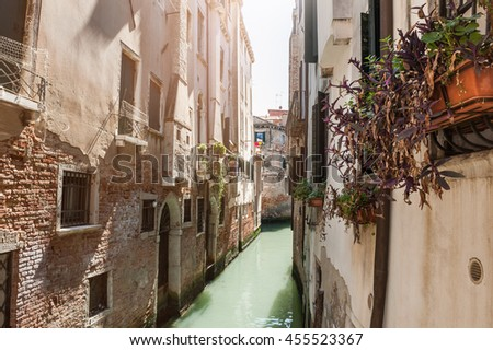 Scenic narrow canal with ancient buildings in Venice, Italy.