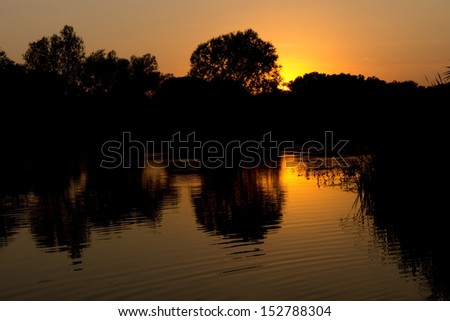 Scenic nature image with sunlight reflected in the surface of a lake at sunset - stock photo