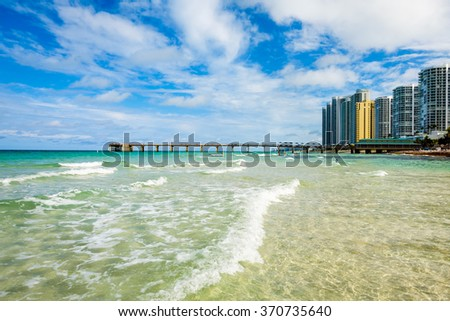 Scenic North Miami Beach skyline with condos, resort hotels, and fishing pier. - stock photo
