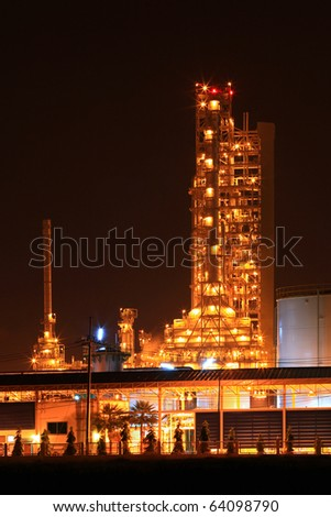 scenic of petrochemical oil refinery plant shines at night, vertical closeup - stock photo