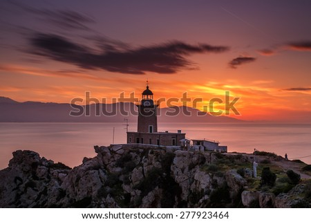 Scenic old lighthouse near Perachora, Greece against a cloudy sky in the sunset - stock photo
