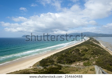 Scenic panorama lookout over The Neck beach on Bruny Island, Tasmania, Australia, with wide bay of southern ocean, mountains blurred background, copy space blue sky. - stock photo