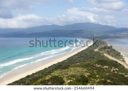 Scenic panorama lookout over The Neck beach on Bruny Island, Tasmania, Australia, with wide bay of southern ocean, mountains blurred background, copy space and blue sky. - stock photo
