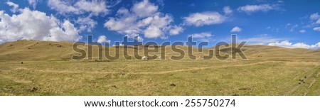 Scenic panorama of green grasslands in Kyrgyzstan with traditional nomadic yurt