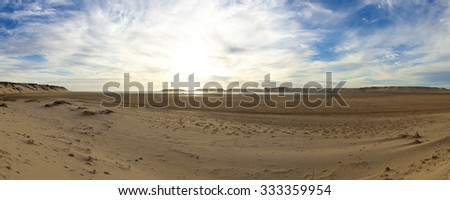 Scenic panorama of sand dunes and the Atlantic ocean with cloudy blue clear sky on Ad Dakhla peninsula in South of Morocco. - stock photo