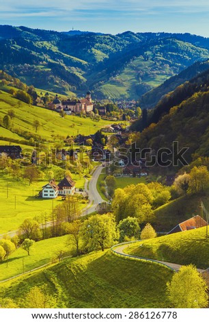 Scenic panorama with a picturesque summer mountain village at sunset in Germany, Muenstertal, Black forest - stock photo