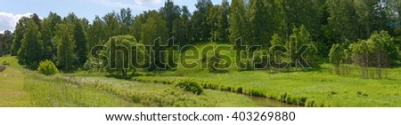 Scenic panoramic view of bright green landscape in sunlight of small valley of Pazha River near Pokrovskyi Park on Gorchakov Street is in Khotkovo, Russia. - stock photo