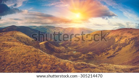 Scenic panoramic view of mountains. Autumn landscape:lake and colorful hills at sunset.Filtered image:cross processed vintage effect.