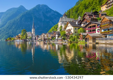 Scenic picture-postcard view of famous Hallstatt lakeside town reflecting  in Hallstattersee lake in the