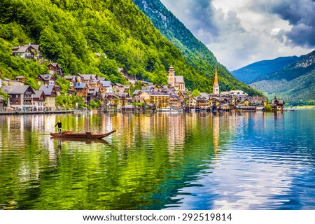 Scenic picture-postcard view of famous Hallstatt mountain village with Hallstaetter See and traditional Plaette boat in the Austrian Alps, region of Salzkammergut, Austria - stock photo